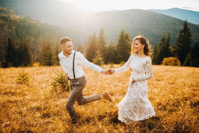 Sunset illuminates mountain hill where wedding couple walks